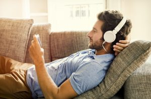 Young male sofa watching video on smartphone at home